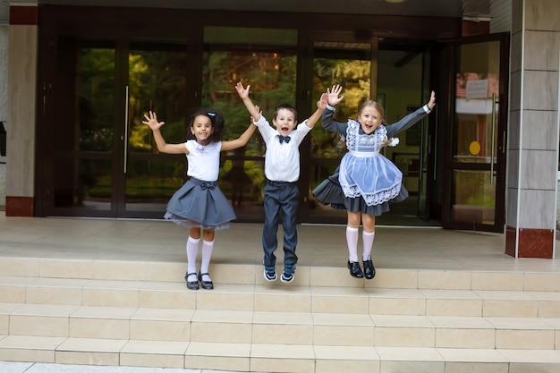 Dzieci uczniowie w mundurkach szkolnych chłopiec blondynka i brunetka skaczą i radują się