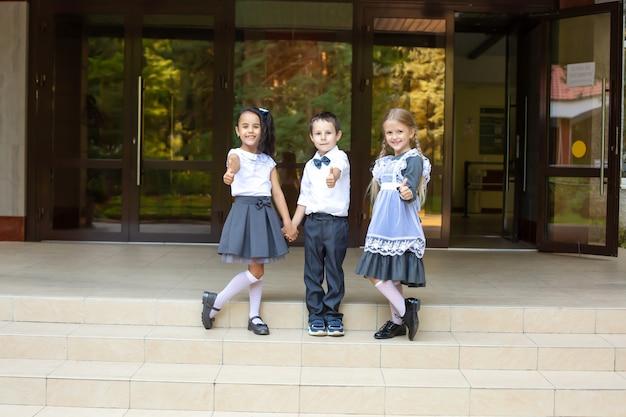 Dzieci uczniowie w mundurkach szkolnych chłopiec blondynka i brunetka stoją