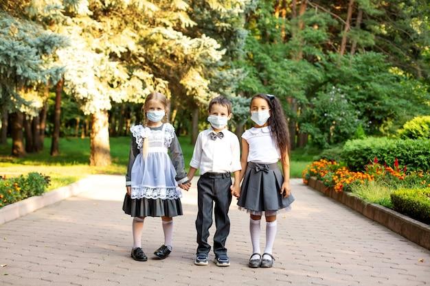 Dzieci uczniowie w mundurkach szkolnych chłopiec blondynka i brunetka