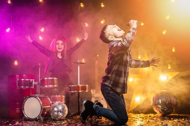 Dzieci udające rockowy zespół grają i śpiewają