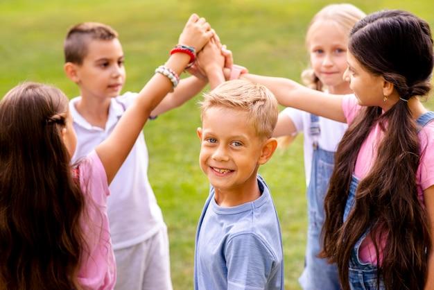 Dzieci układają razem swoje prawe ręce