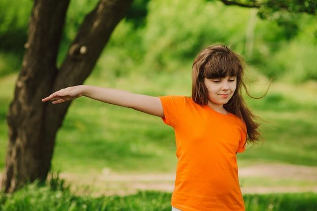 Dzieci uprawiają sport na zewnątrz. dziewczyna robi joga outdoors na zielonej trawie