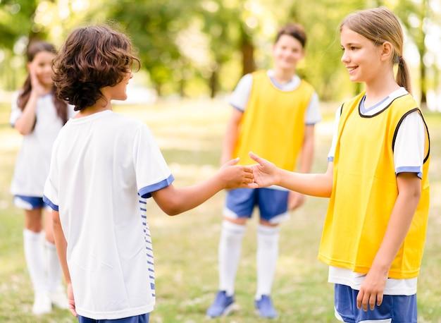 Dzieci uścisk dłoni przed meczem piłki nożnej
