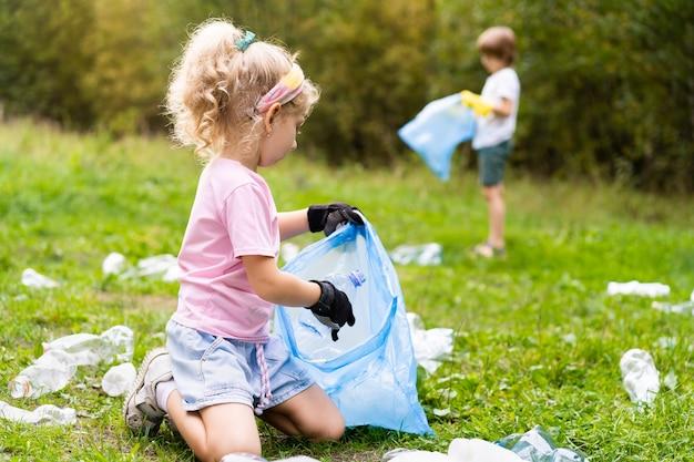 Dzieci usuwają plastikowe śmieci i wrzucają je do biodegradowalnego worka na śmieci na świeżym powietrzu. pojęcie ekologii, przetwarzania odpadów i ochrony przyrody. ochrona środowiska.