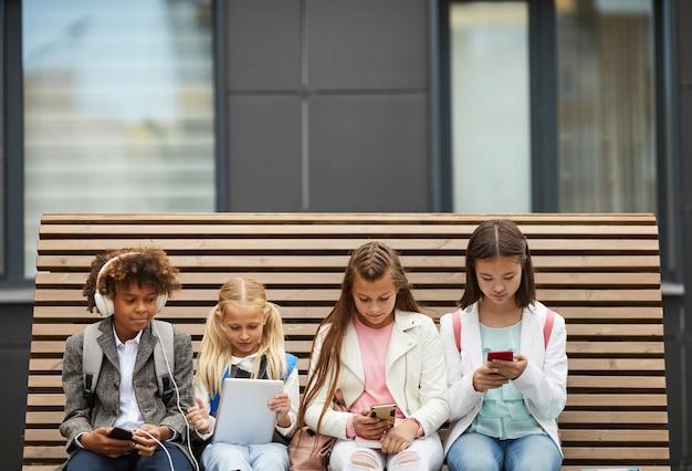 Dzieci używające gadżetów na zewnątrz
