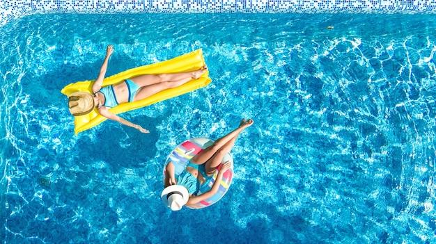 Dzieci w basenie widok z lotu ptaka z drona powyżej, szczęśliwe dzieci pływają na dmuchanym pączku i materacu, aktywne dziewczyny bawią się w wodzie na rodzinnych wakacjach w ośrodku wypoczynkowym