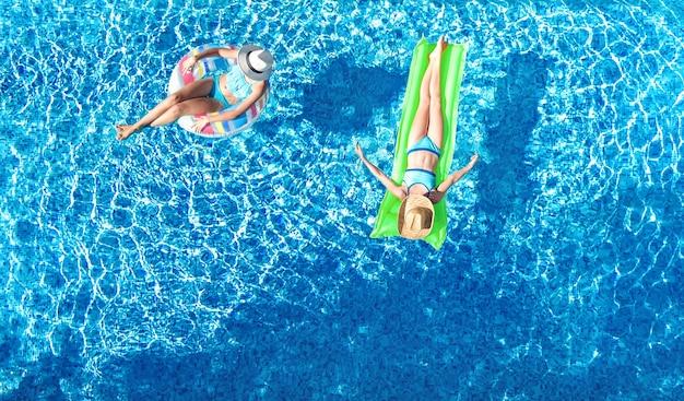 Dzieci w basenie z lotu ptaka z lotu ptaka szczęśliwe dzieci pływają na nadmuchiwanym pierścieniu pączka