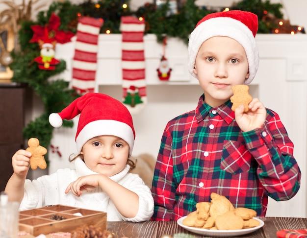 Dzieci w czapce mikołaja ze świątecznymi ciasteczkami w domu.