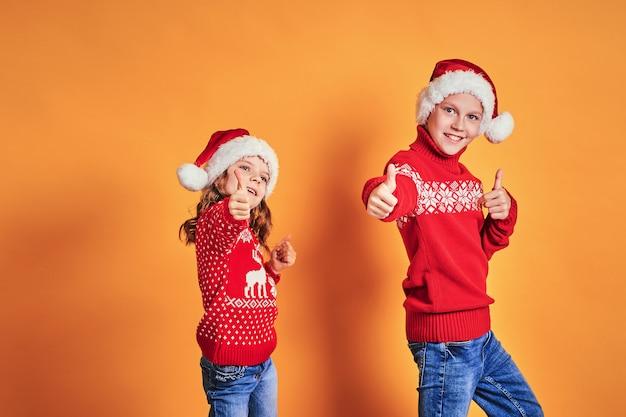 Dzieci w czapkach świętego mikołaja z kciuki do góry