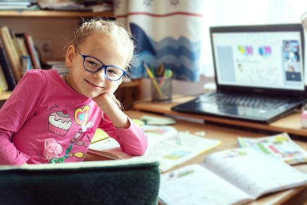 Dzieci w domu, szczęśliwa mała dziewczynka siedzi przy stole z laptopem i podręcznikami szkolnymi