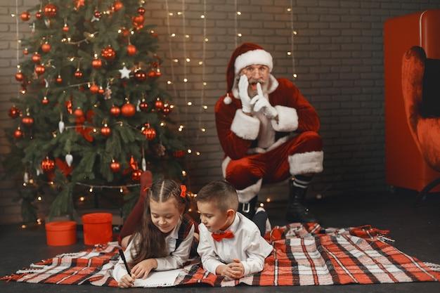 Dzieci w domu, udekorowane na boże narodzenie. poczta świętego mikołaja.