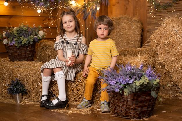 Dzieci w gospodarstwie w stodole siedzi w snopy słomy