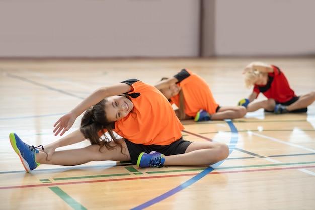 Dzieci w jasnej odzieży sportowej, ćwicząc na siłowni