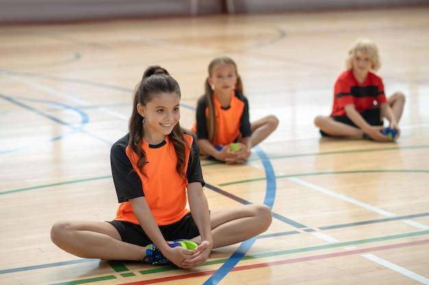 Dzieci w jasnej odzieży sportowej rozciągające nogi