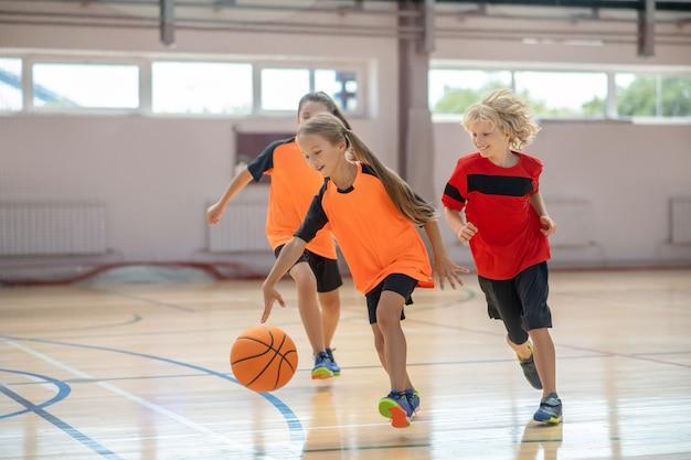 Dzieci w jasnych strojach sportowych grające w koszykówkę i wyglądające na podekscytowane