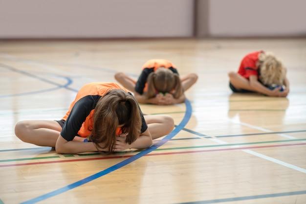 Dzieci w jasnych strojach sportowych rozciągają się i pochylają do przodu