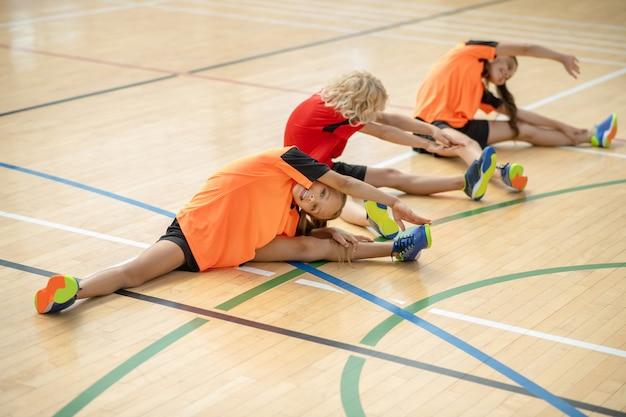 Dzieci w jasnych strojach sportowych siedzą na podłodze i się rozciągają