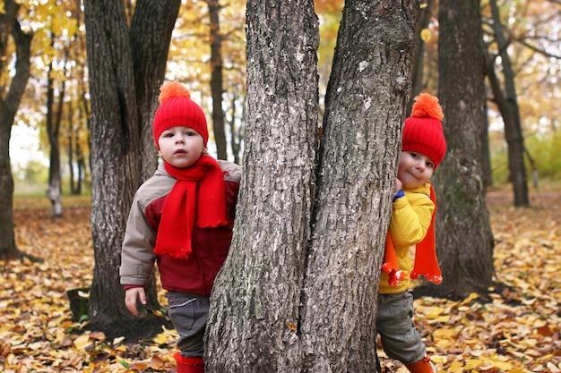 Dzieci w jesiennym parku z dynią wokół jesiennych liści