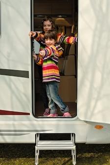 Dzieci w kamperu bawią się, rodzinne podróże samochodem kempingowym podczas wakacyjnych wakacji na kempingu