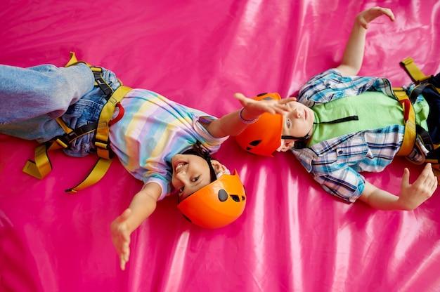 Dzieci w kaskach leżące na matach, młodzi wspinacze