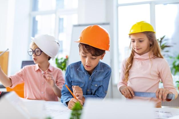 Dzieci w kaskach. uczniowie w hełmach czują się radośni podczas wykonywania szkiców budowlanych