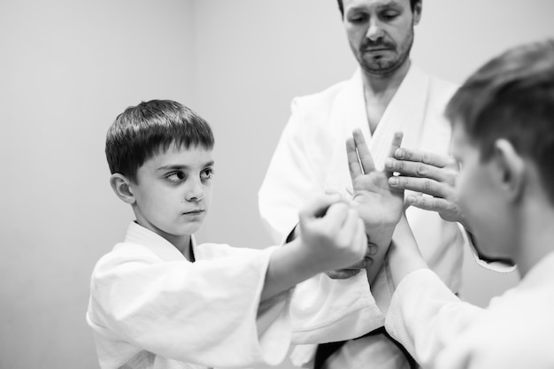 Dzieci w kimonie rozpoczynają trening na aikido.