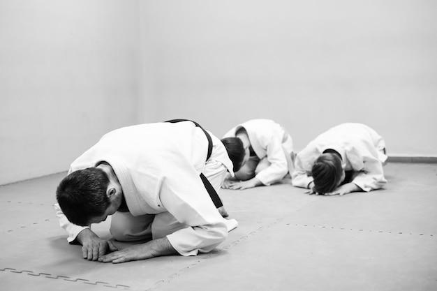 Dzieci w kimonie siedzą na tatami z trenerem na seminarium poświęconym sztukom walki