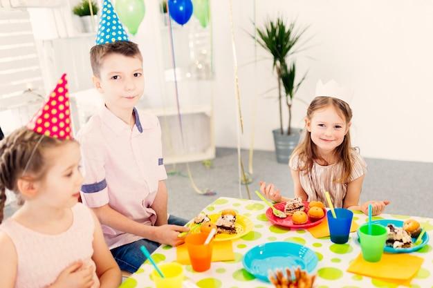 Dzieci w kolorowych czapkach patrząc na kamery