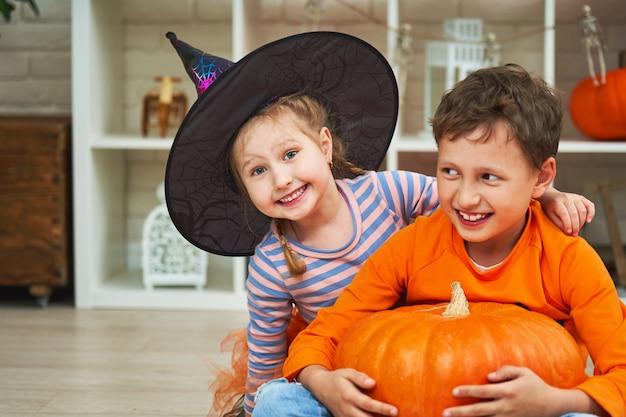 Dzieci w kostiumach na halloween bawią się w urządzonym pokoju