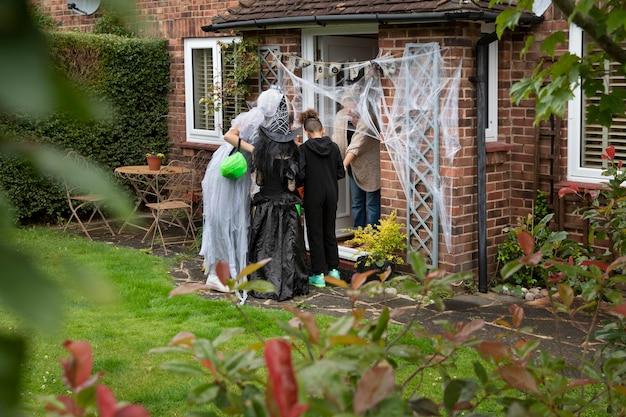 Dzieci w kostiumach oszukują lub traktują w czyimś domu
