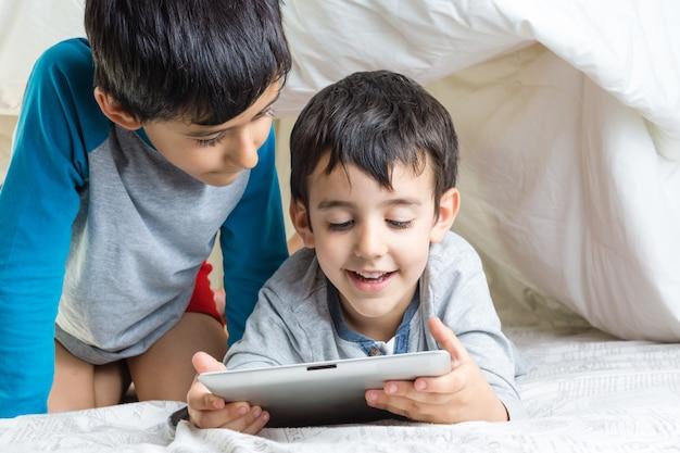 Dzieci w łóżku z tabletem