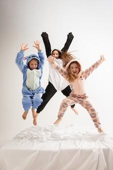 Dzieci w miękkiej ciepłej piżamie w jasnym kolorze bawią się w domu. małe dziewczynki bawią się, bawią, śmieją się, skaczą razem, wyglądają stylowo i szczęśliwie. pojęcie dzieciństwa, spędzania wolnego czasu, szczęścia.