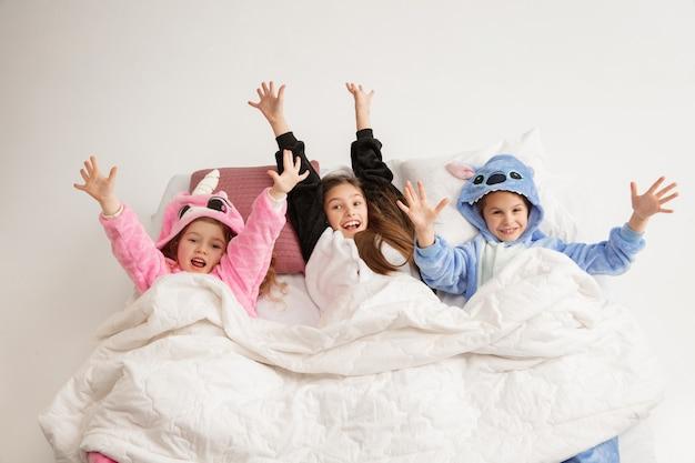 Dzieci w miękkiej ciepłej piżamie w jasnym kolorze bawią się w domu. małe dziewczynki bawią się, imprezują, śmieją, bawią się razem, wyglądają stylowo i szczęśliwie. pojęcie dzieciństwa, spędzania wolnego czasu, szczęścia.