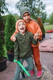 Dzieci w modnych czapkach i bluzach bawiące się w parku jesienne klimaty jesienna uroda styl moda dziecięca