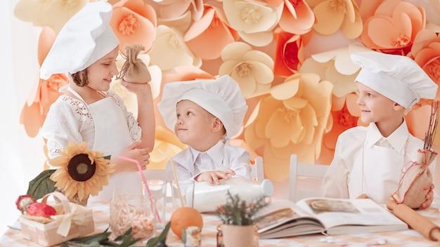 Dzieci w mundurach szefów kuchni stojących w pobliżu stołu w kuchni. zdjęcie z miejsca na kopię
