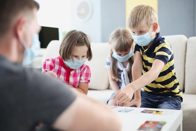 Dzieci w ochronnych maskach medycznych grają w gry planszowe z rodzicami przy stole