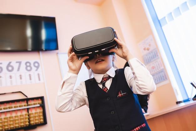 Dzieci w okularach rzeczywistości wirtualnej są w szkolnym biurze