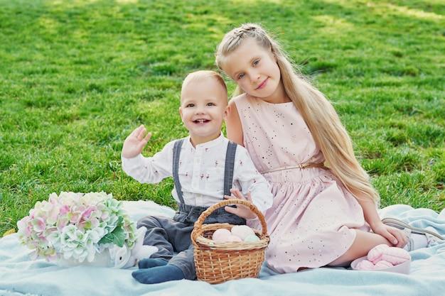 Dzieci w parku na wielkanocnym pikniku z jajkami i królikiem