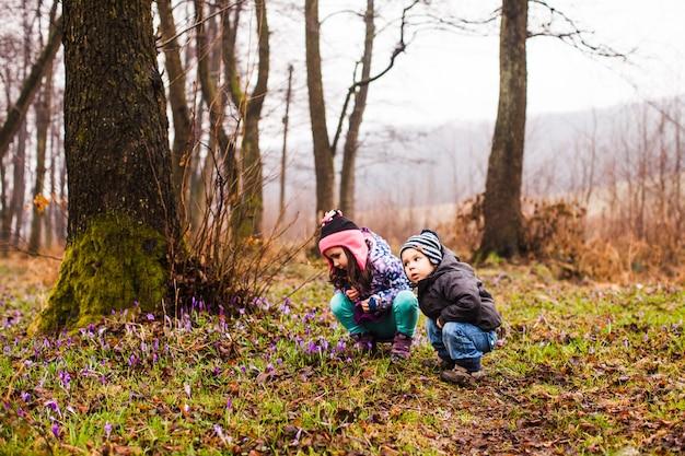 Dzieci w parku oglądają wiosenne kwiaty w pochmurny deszczowy dzień