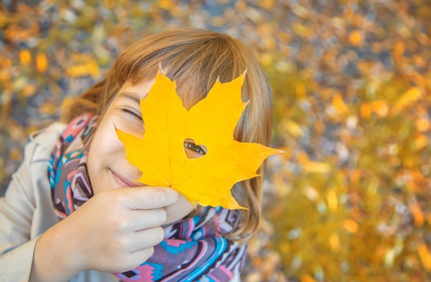 Dzieci w parku z jesiennych liści. selektywne ustawianie ostrości.