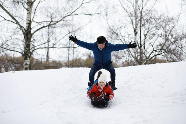 Dzieci w parku zimą. dzieci bawią się śniegiem na placu zabaw. rzeźbią bałwany i zjeżdżają ze wzgórz.