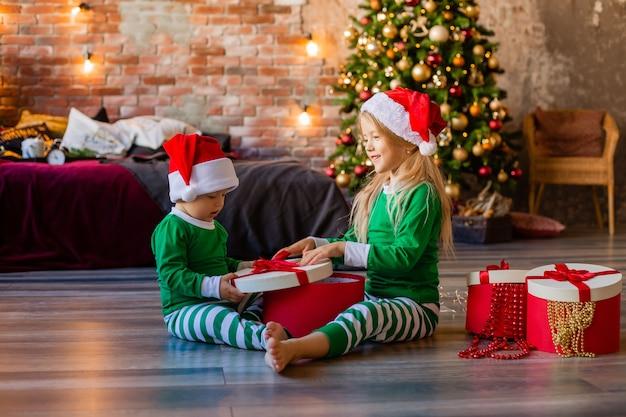 Dzieci w piżamach i czapkach rozpakowują świąteczne prezenty
