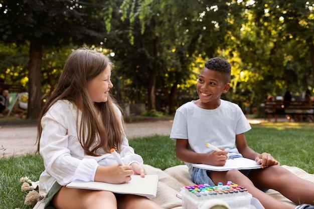 Dzieci w średnim ujęciu rysują razem