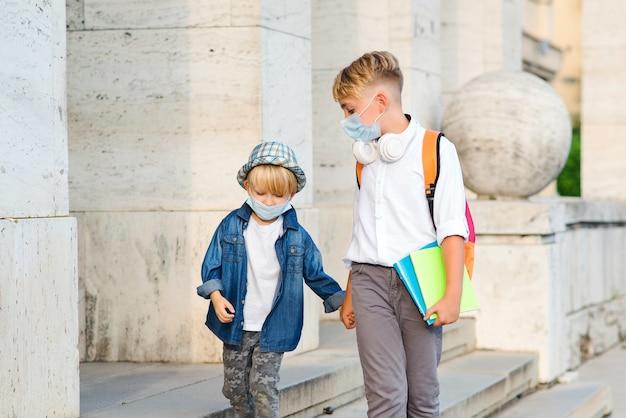 Dzieci w szkole chodzą na zewnątrz w maskach na twarz