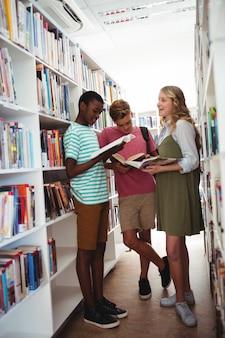Dzieci w szkole czytają książki w bibliotece w szkole