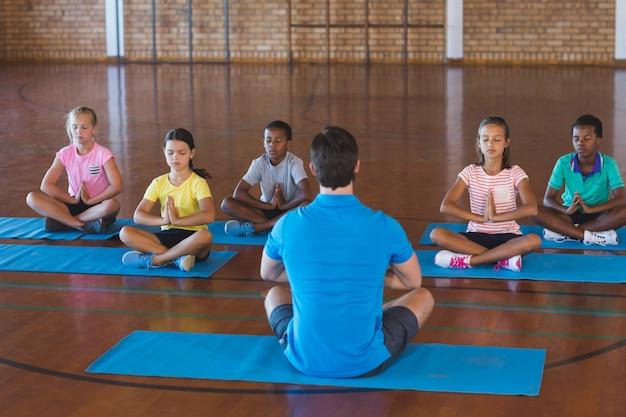 Dzieci w szkole i nauczyciel medytujący podczas zajęć jogi