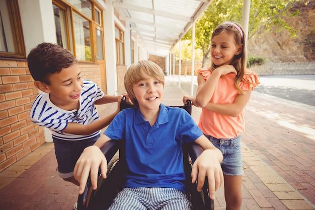 Dzieci w szkole rozmawia z chłopcem na wózku inwalidzkim