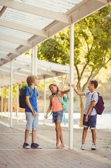 Dzieci w szkole rozmawiają ze sobą na szkolnym korytarzu