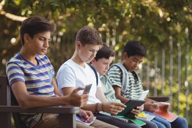 Dzieci w szkole za pomocą telefonu komórkowego i cyfrowego tabletu na ławce