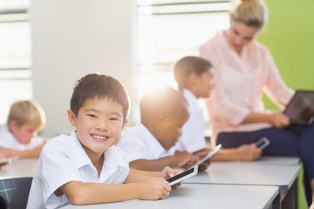 Dzieci w szkole za pomocą telefonu komórkowego w klasie